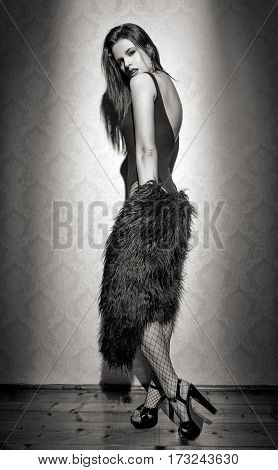 Sensual woman posing at vintage wall black and white take off fur coat