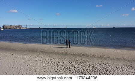 Woman and man are standing on the beach and look at the dark blue sea