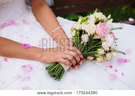 boquet of rose flowers in bride hands with rose petals on dress