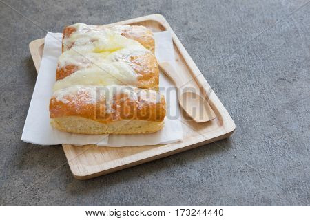 Sweet butter bread topping with butter and sugar on wooden tray