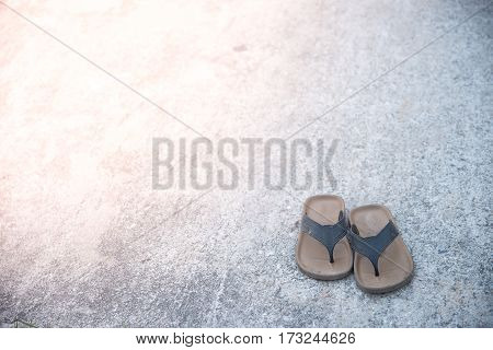 Old slippers put on the old cement floor.