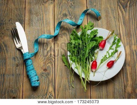 Fresh healthy salad and measuring tape on rustic table. Healthy food top view .