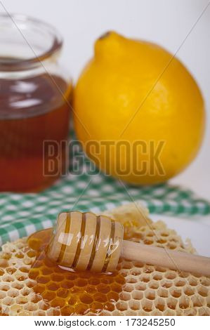 Honey in  jar with honey dipper and lemon on a wooden background