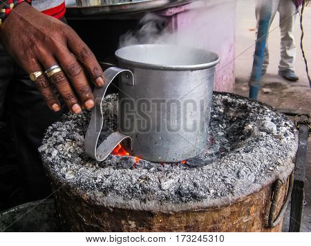 India. The man on street oven boils drink in an aluminum mug. Traditional Indian outdoor oven.
