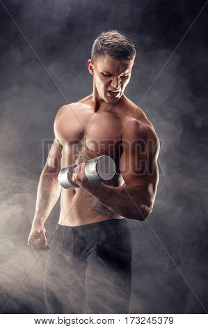 Handsome bodybuilder doing exercise on biceps with dumbbell. Studio shot. Smoke.