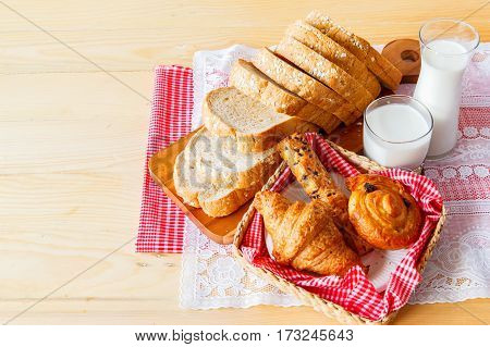 fresh bread and wheat Served with a glass of milk on the wooden brackground Healthy eating concept