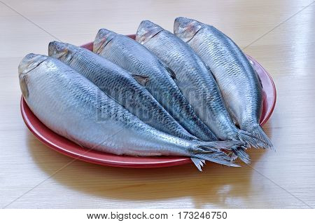 five fresh fish salted herring lie on ceramic brown the dish and wooden table
