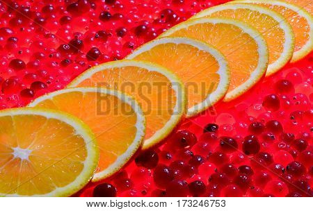 a lot of round orange slices upon each other diagonally on ripe red cranberries that glow like the coals of a campfire