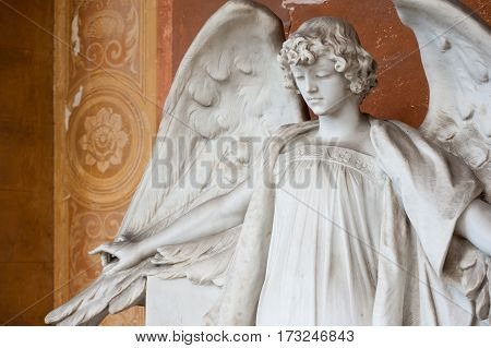 The marble angel with outstretched wings with his eyes down