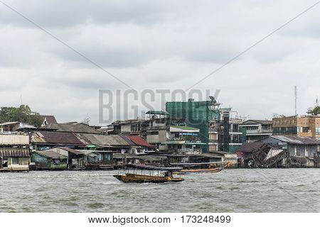 Bangkok Thailand Long tail boat on river chao Phraya in Bangkok poor houses ruins