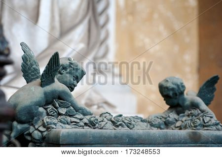 Two cherubs climb a full of roses altar glancing sideways