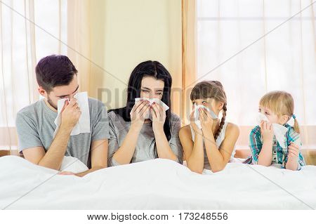Sick Family Lying In Bed At Home