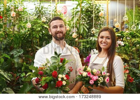 Male and female florists with beautiful bouquets in greenhouse