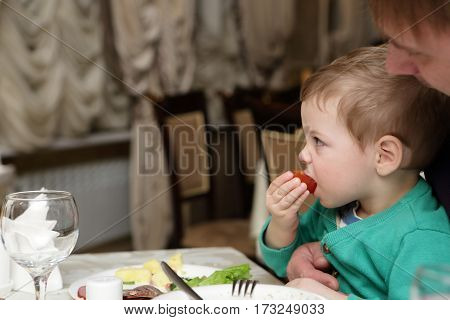 Boy is eating tomato in a restaurant