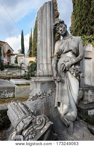 The young sad grieving woman statue leaning on the column at the cemetery holding flowers in her hand
