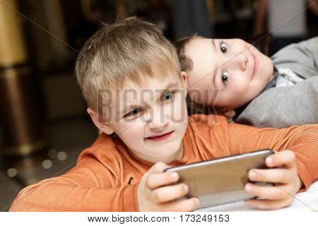 Two children playing in smartphone in cafe