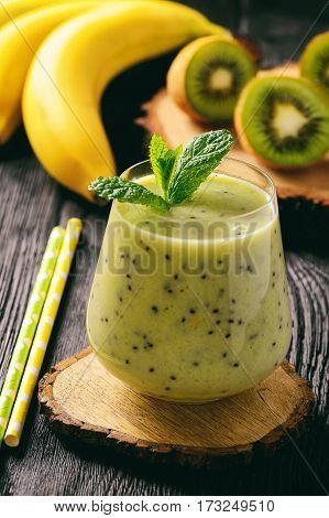 Banana and kiwi smoothie on dark wooden background.