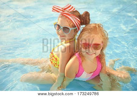 Little girls in swimming pool on sunny day