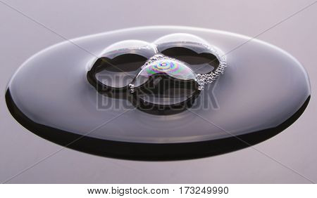 Big water drop with three bubbles on drak grey surface