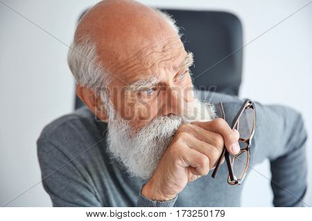 Old man with glasses sitting in arm chair on light background