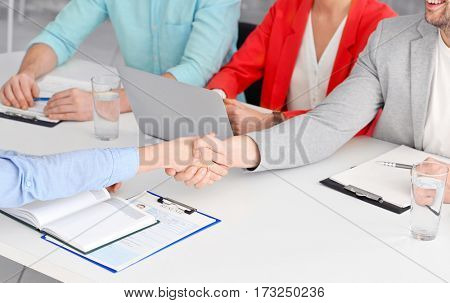 Job interview concept. HR manager shaking female hand in office