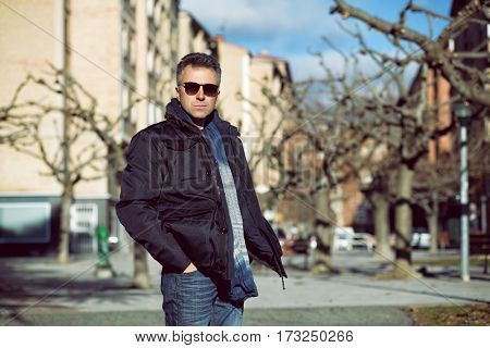 Handsome happy smiling man. Outdoor winter male portrait. Attractive confident middle-aged man in sunglasses walking in city.