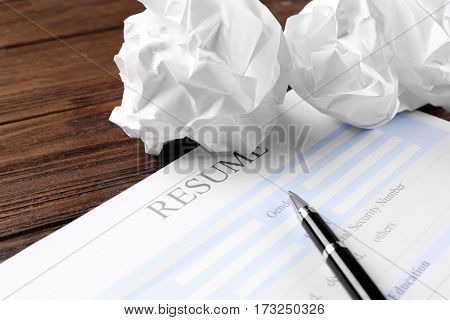 Blank resume form and crumpled paper on wooden table, closeup