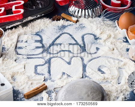 Flour letters spelling Baking with tools and sweet food ingredients sugar, eggs, cocoa, cinnamon. Top view flat lay concept