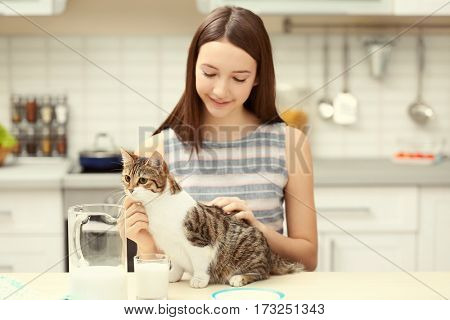 Morning of beautiful young woman and cat in kitchen