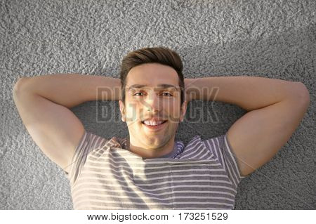 Happy young man lying on soft floor in light room