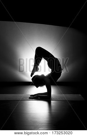 Woman doing yoga scorpion pose silhouette black and white in studio