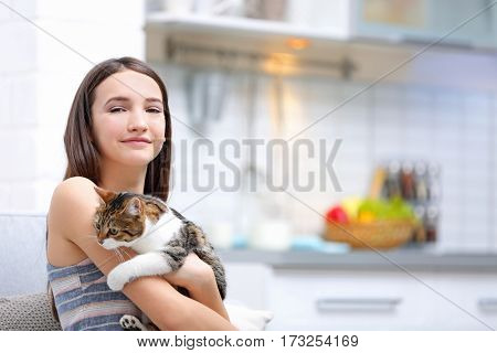 Beautiful young woman with cute cat at home