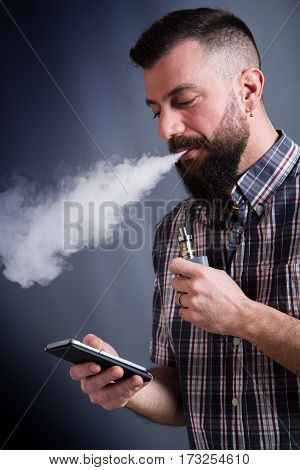Beared Man  Smoking Electronic Cigarette Looking To The Smartphone