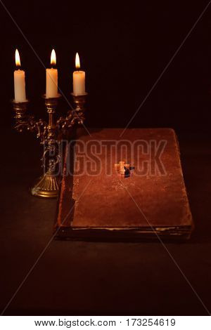 Bible and burning candles on table