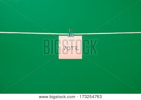 Pink Paper Note On Clothesline With Text Vote