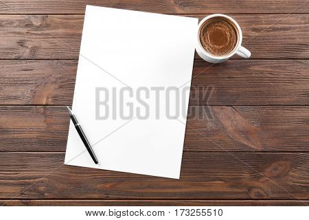 Cup of coffee and paper with pen on wooden table