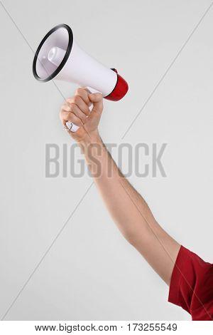 Male hand holding megaphone on light background