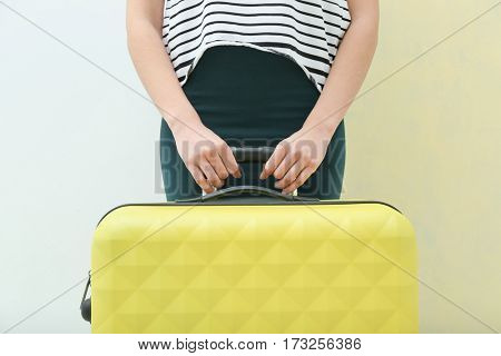 Young tourist with suitcase on light background