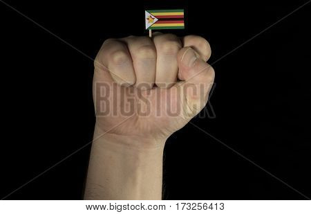 Man Hand Fist With Zimbabwean Flag Isolated On Black Background