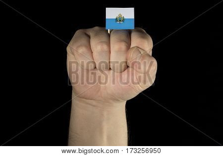 Man Hand Fist With San Marino Flag Isolated On Black Background