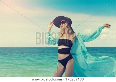 Attractive young woman in bikini and hat on a background of sea beach.