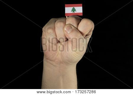 Man Hand Fist With Lebanese Flag Isolated On Black Background