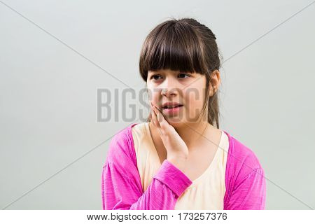 Little girl is having toothache and she is very worried.
