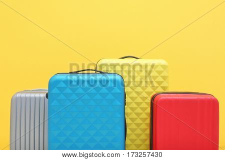 Packed travel suitcases on yellow background