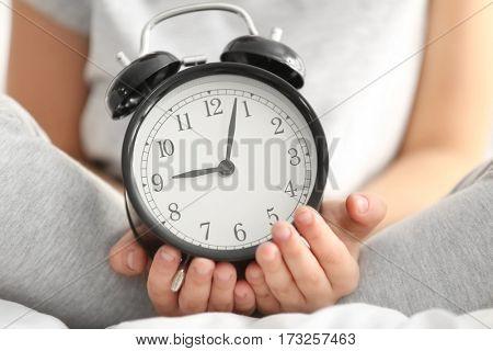 Cute little child with alarm clock, closeup