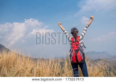 Woman Traveler hands raised hiking Travel Lifestyle concept Summer vacations outdoor mountains on background view from the ground