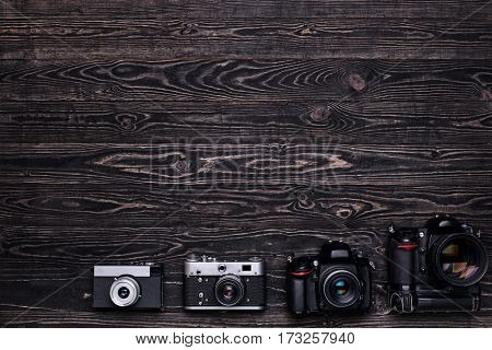 Old retro and modern digital camera on dark wooden table