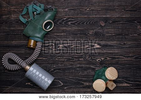 Old gas mask and respirator on dark wooden table.Top view
