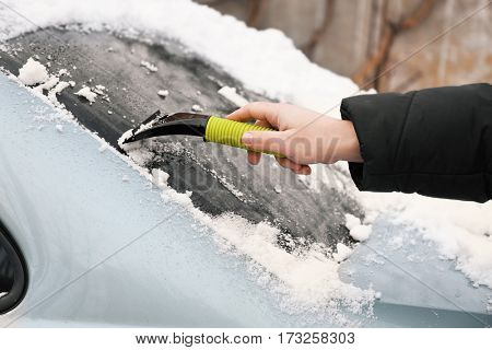 Man removing snow from car with scraper