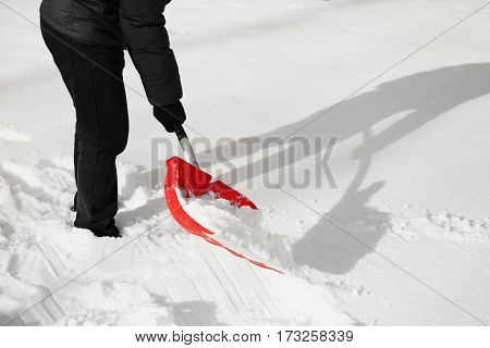Man removing snow with red shovel